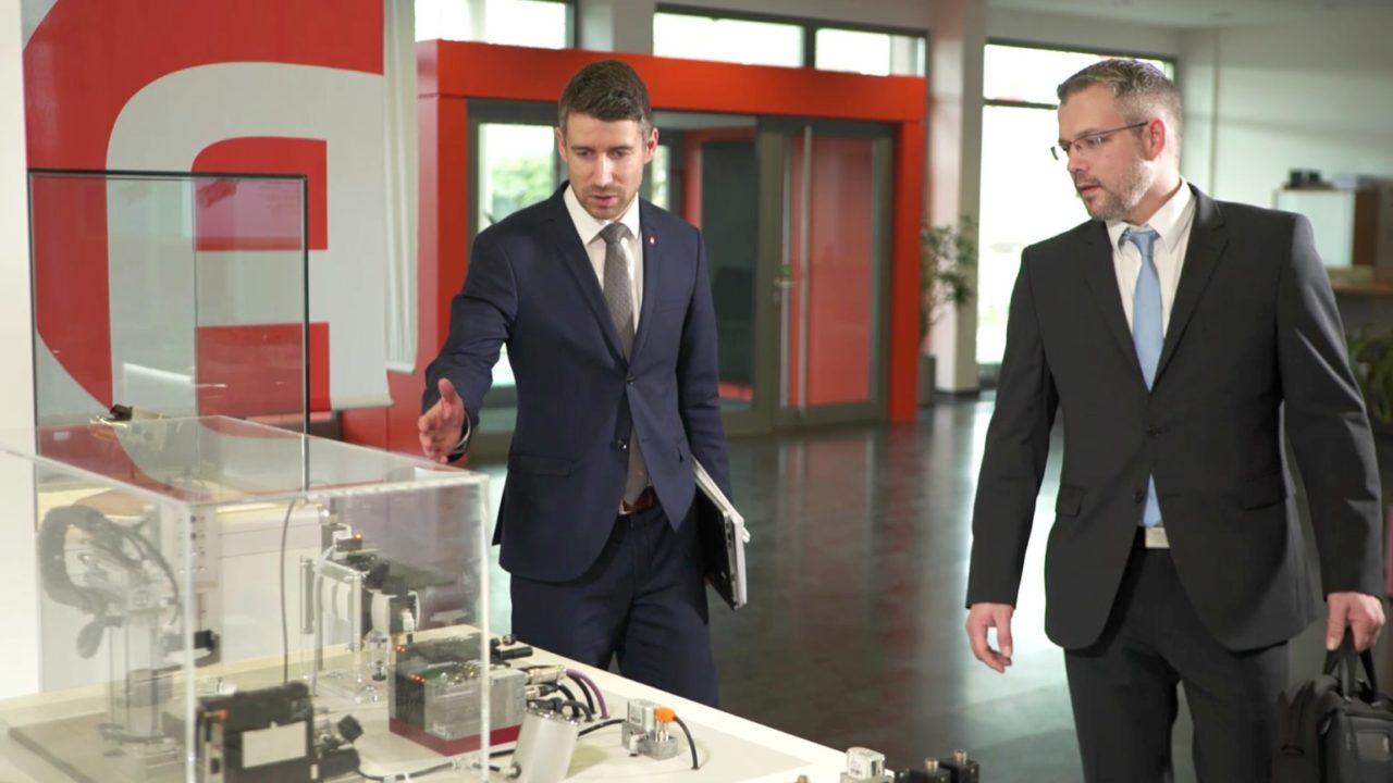 """tecmotion - Ausschnitt 02 aus dem AVENTICS-Imagefilm """"Systemtechnik"""", Mitarbeiter im Foyer an einem Produktschaukasten"""